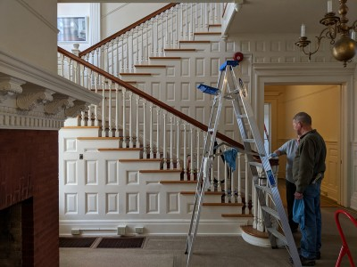 NPS staff clean the woodwork on the stairway at Flat Top Manor at Moses H. Cone Memorial Park.