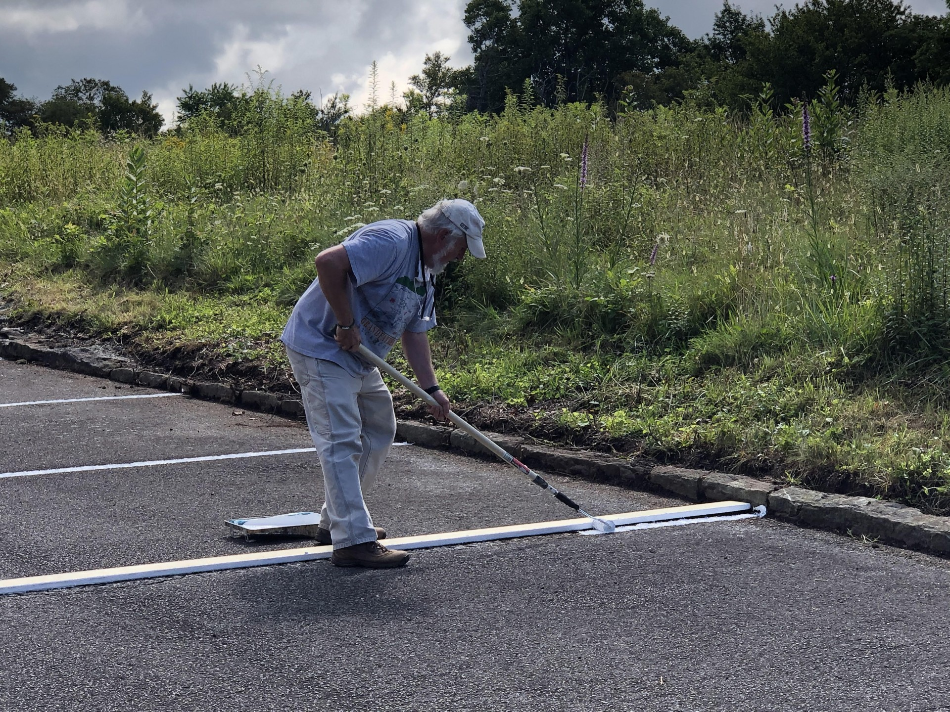 A volunteer stripes the parking lot with paint at The Bluffs Restaurant