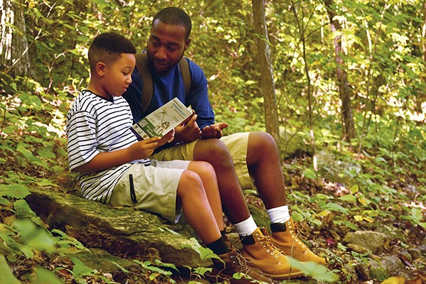 A father and son use a Kids in Parks TRACK Trail brochure to explore the forest.