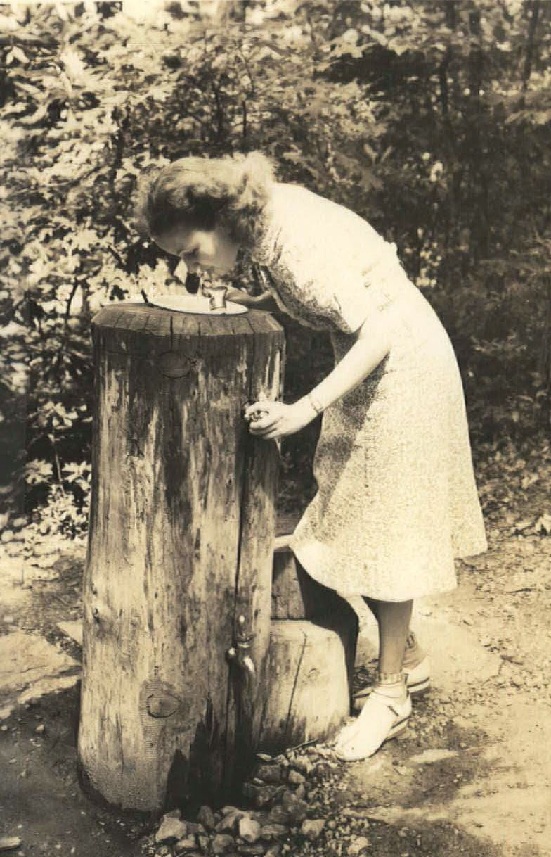 A woman drinks from a log water fountain in 1940 at Cumberland Knob, the first recreation area along the Blue Ridge Parkway.